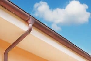 brown copper gutter under a cloudy sky