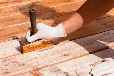 fix wood rot Painter staining deck boards with transparent protective outdoor decking paint applying stain with brush with special attention to the gaps